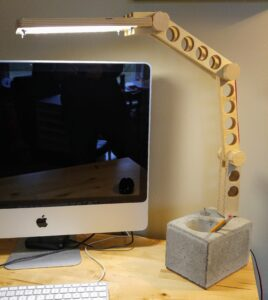 A concrete base with integrated toggle switch anchors the articulating baltic birch ply arm, ending in an LED panel that floods the workspace with light